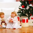 Two happy twins girl sitting with gift boxes near Christmas tree — Stock Photo #8996966