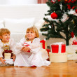 Two happy twins girl sitting with gift boxes near Christmas tree — Stock Photo