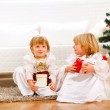 Two cute twins girl sitting with presents boxes near Christmas t — Stock Photo #8996968