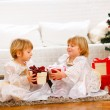 Two lovely twins girl exchanging presents near under Christmas t — Stock Photo