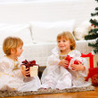 Two twins girl sitting with presents near Christmas tree — Stockfoto