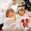 Two twins girls sitting with presents near Christmas tree — 图库照片