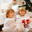 Two twins girls sitting with presents near Christmas tree — Stockfoto