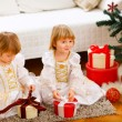 Two cute twins girls opening presents near Christmas tree — Stockfoto
