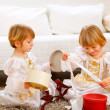 Two cute twins girls opening presents near Christmas tree — ストック写真