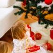 Two girls opening presents near Christmas tree — Стоковое фото