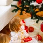 dvě dívky otevření představuje poblíž vánoční stromeček — Stock fotografie