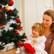 Stock Photo: Family spending time near Christmas tree