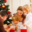 Mom and dad looking with twins daughters inside of Christmas soc — Stock Photo #8997013