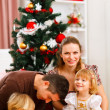 Parents with two daughters spending time near Christmas tree — Stock Photo