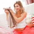 Smiling pregnant examines purchases for baby — Stock Photo #8998636