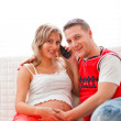 Happy pregnant woman with husband speaking mobile phone — Stock Photo #8998641