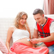 Stock Photo: Young guy listening baby in his pregnant wifes belly using steth