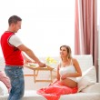 Young guy bring breakfast to happy pregnant wife — Stock Photo #8998663