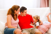 Mother father sitting on couch and talking with daughter — Stock Photo