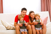 Mother and father playing with twins daughter on console — Foto Stock