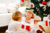 Happy girl sitting near Christmas tree and presenting gift to he — Stock Photo