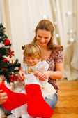 Mom looking with daughter inside of Christmas socks near Christm — Stock Photo