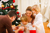 Mom and dad looking with twins daughters inside of Christmas soc — Stock Photo