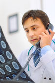 Medical doctor holding patients tomography and speaking phone — Stockfoto