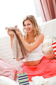 Smiling pregnant examines purchases for baby — Stock Photo