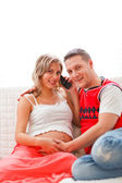 Happy pregnant woman with husband speaking mobile phone — Foto Stock