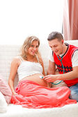 Young guy listening baby in his pregnant wifes belly using steth — Stock Photo