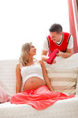 Young husband making present to pregnant wife — Foto Stock