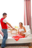 Young guy bring breakfast to happy pregnant wife — Stok fotoğraf