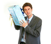 Modern businessman shaking present box trying to guess what's in — Stock Photo