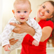 Stock Photo: Happy mother and lovely baby playing on divan
