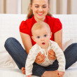 Interested baby playing on mothers laps — Stock Photo #9000880