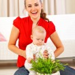Smiling mommy showing plant to her baby — Stock Photo #9000891