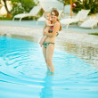 Happy young mother with baby standing in swimming pool — Stock Photo