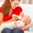 Happy mother sitting on sofand feeding baby — Stock Photo #9001349