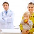 Portrait of mother with baby holding apple and doctor in backgro — Stock Photo