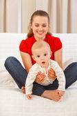 Interested baby playing on mothers laps — Stock Photo