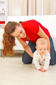 Mother helping cheerful baby learn to creep — Stock Photo