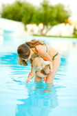 Mother showing water to baby standing in swimming pool — Stock Photo