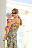 Portrait of mother holding baby on street — Stock Photo