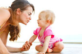 Young mother playing with baby on floor — Stock Photo