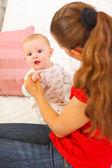 Interesse baby spelen met moeders op bank — Stockfoto