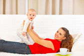 Smiling mother and adorable baby playing on couch — Stock Photo