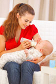 Happy mother sitting on sofa and feeding baby — Stock Photo