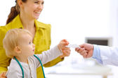 Mother and baby stretching for prescription in hand of pediatric — Stock Photo