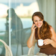 Happy girl speaking cell phone and having cup of coffee at terra — Stock Photo #9428465
