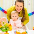 Stock Photo: Smiling mother and eat smeared baby on birthday celebration part