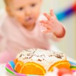 Closeup on birthday cake and eat smeared baby in background — Stock Photo
