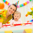 Stock Photo: Smiling mom and eat smeared baby on birthday celebration party