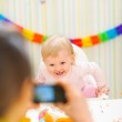 Mother making photos of happy baby on first birthday party — Stock Photo